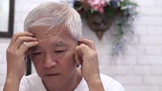 video of Asian senior guy with hand on face thinking, worry and sad