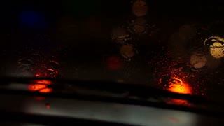 Video of beautiful colorful blurry light of traffic outside on the road. Rain flows and wipers on the car front windshield glass