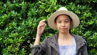 Video of Beautiful smiling Asian woman closeup portrait. Wearing hat with natural green bush background. modern life condominium