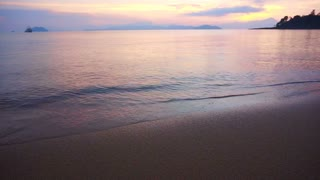 Video of beautiful sunrise sand beach and calm sea. Pink, purple and blue sky