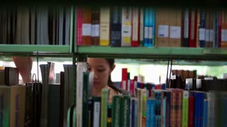 Video of Female, girl student walking between shelves, searching for books in library