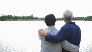 Video of Happy asian senior couple, talking and looking at the lake with mountain background