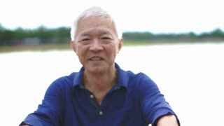 Video of Happy asian senior man smiling happy in park with lake background