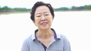 Video of Happy asian senior woman smiling happily in front of nature lake