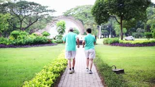 Video of healthy asian senior couple exercise and walk together through the park
