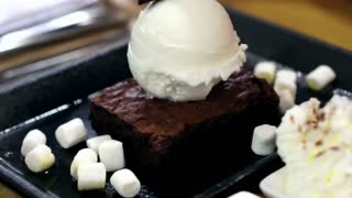 Video of Marshmallow and ice cream waffle with melt hot chocolate topping pour on hot plate