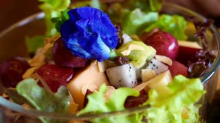 Video of purple flowers on fresh vegetables and fruits salad
