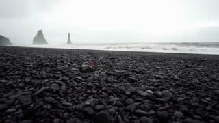 4K Black sandy lava beach in Vik, Iceland. Low angle, tilt up landmark beach near basalt sea stacks