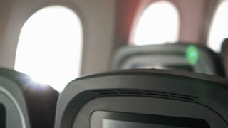 Airplane interior RF view of seats, windows and passenger in queue after arrival