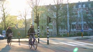 Amsterdam, Netherlands - 4 April 2017 : People biking after work, green city at sunset