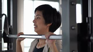 Asian adult female athlete exercising in fitness gym doing machine weight lifting