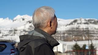 Asian senior man looking at snow mountain and thinking. Abstract midlife crisis problem