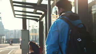 Asian backpacker man looking confuse and lost at tram station slow motion 120 fps shot