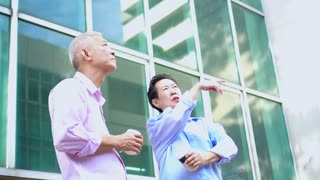 Asian elderly couple looking for property in urban city downtown