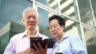 Asian elderly couple looking for property information tablet