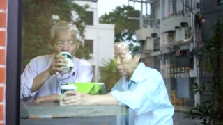 Asian elderly couple spill while drinking coffee taking care of each other