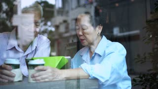 Asian elderly couple using pad in coffee shop, modern technology for senior