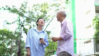 Asian elderly couple walking in urban city building with take away morning coffee