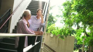 Asian elderly professional couple talking outdoor morning in city modern building