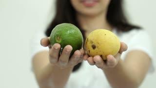 Asian girl hands show fruits, avocado and mango for good health concept