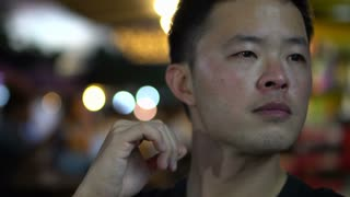 Asian man hanging out at night thinking about future alone