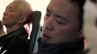 Asian man looks tired and try to sleep during flight on airplane