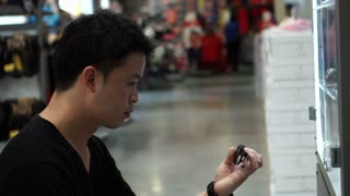 Asian man shopping for guy gadget and accessories in mall 4k