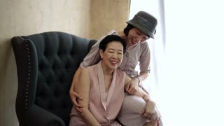 Asian mother and daughter hug, laugh have fun together at home interior background