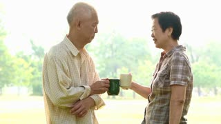 Asian senior couple celebrate life with coffee in park