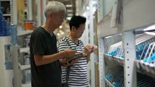Asian senior couple choosing water pipe in home construction mall. Using pad to look up for information online