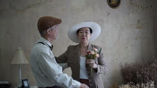 Asian senior couple dating in vintage dress giving flowers