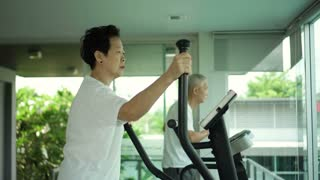 Asian senior couple exercise in gym surrounding with glass and nature
