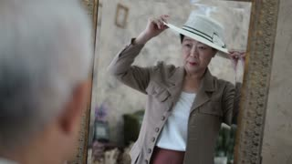 Asian senior couple help each other dress up retro style in front of mirror video