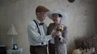 Asian senior couple in retro dress help setting cloth to each other love abstract 4k