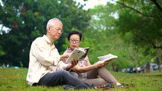 Asian senior couple reading books at the park.Spend quality time and never stop learning something new