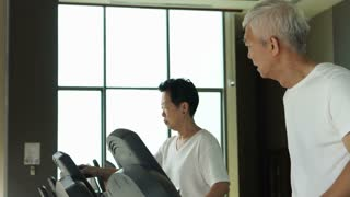Asian senior couple running on a treadmill at the gym healthy lifestyle exercise