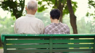 Asian senior couple shot from back sitting in park reading book together