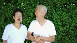 Asian senior couple smiling happy with plant wall green background