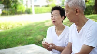Asian senior couple talk about future after retirement in green residence park