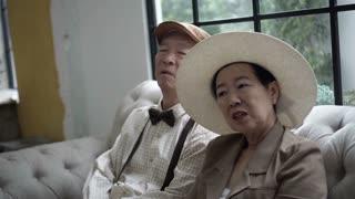 Asian senior couple talk in retro house
