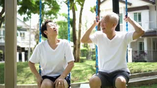 Asian senior couple talking relax at park swing fun