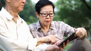 Asian senior couple using tablet together in park