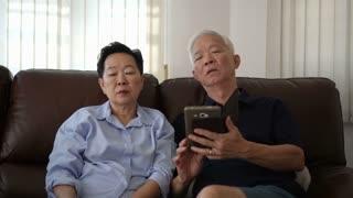 Asian senior couple using two screens conversation