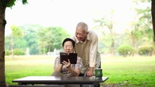 Asian senior laughing using pad for digital communication