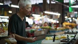 Asian senior man buying food at local market stall