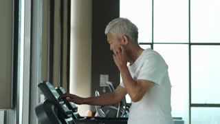 Asian senior man running on a treadmill at the gym healthy lifestyle exercise