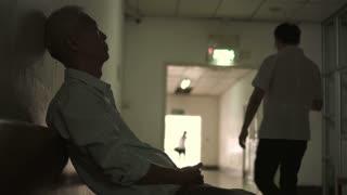 Asian senior man sad worry alone in hospital hallway
