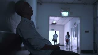 Asian senior man sad worry and scare alone in hospital hallway