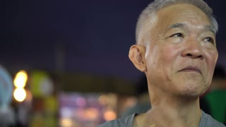 Asian senior man sitting outside in restaurant district hanging out for at night