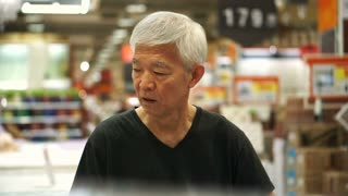 Asian senior man thinking and calculating at store before buying stuffs